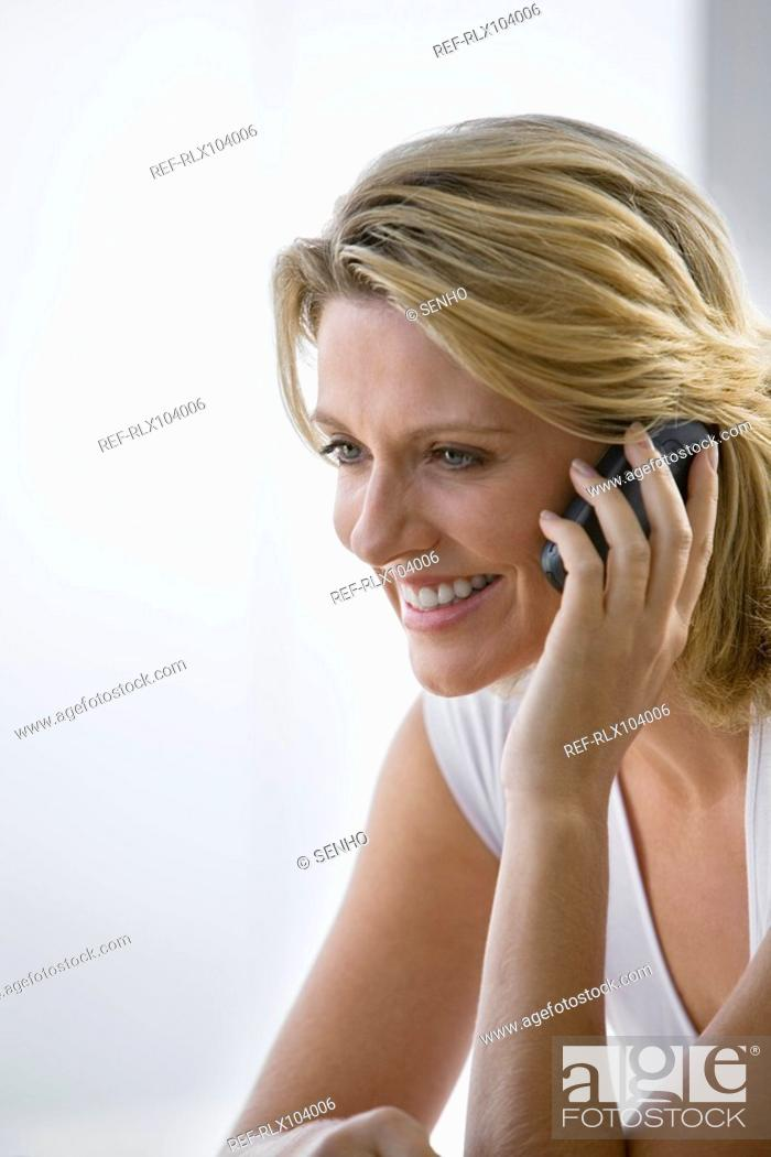 Stock Photo: Mature woman smiling while using Cell phone, portrait.