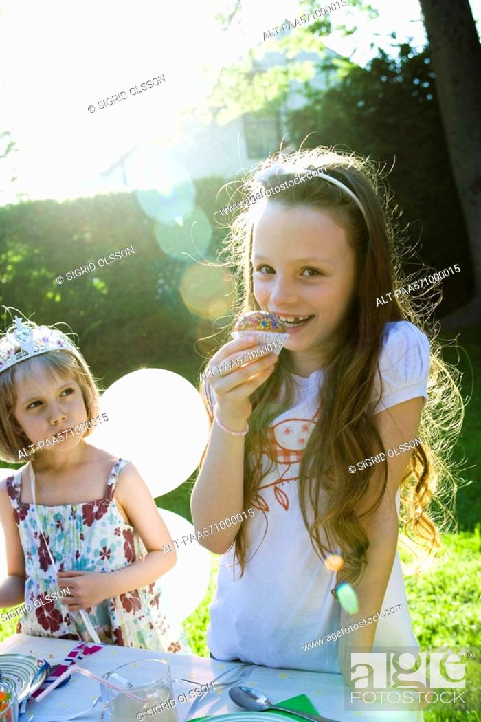 Stock Photo: Girls eating sweets at birthday party.