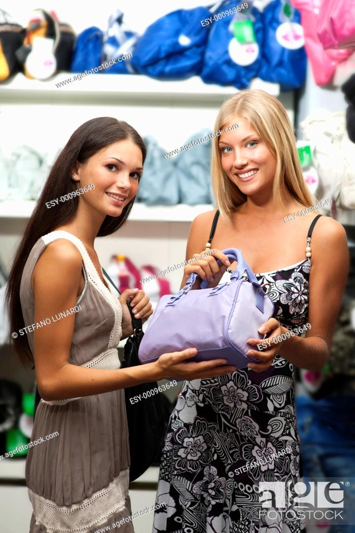 Stock Photo: Beautiful young women inside a bags shop.
