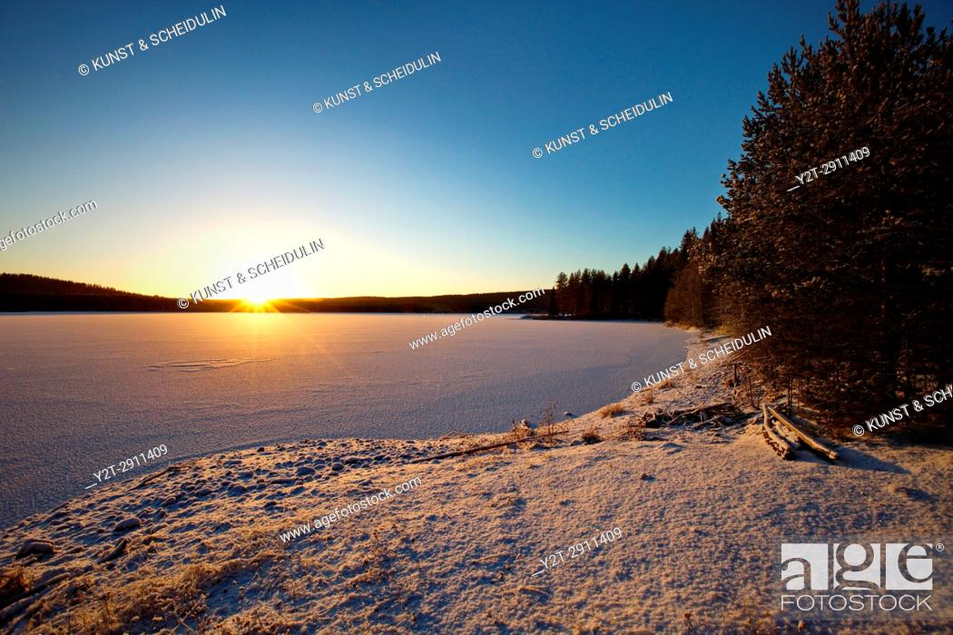 Stock Photo: An ice covered lake in northern Sweden is illuminated by the low winter sun. Agnsjön, Bredbyn, Västernorrland, Sweden.