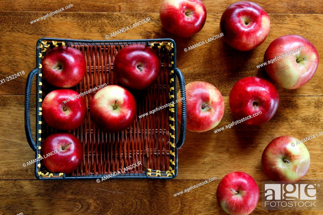 Imagen: Birds eye view of several Apples scattered, inside and outside a basket on wood background.