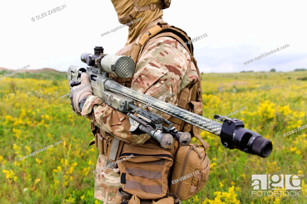 Imagen: Soldier with sniper rifle standing in blooming green field.