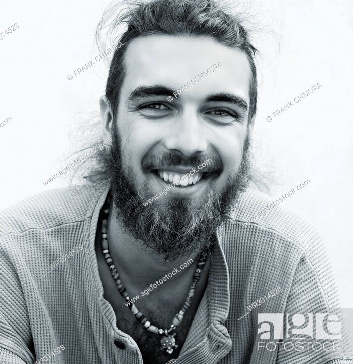 Stock Photo: Portrait of a Teenage Boy with Long Hair and Beard Outdoors.