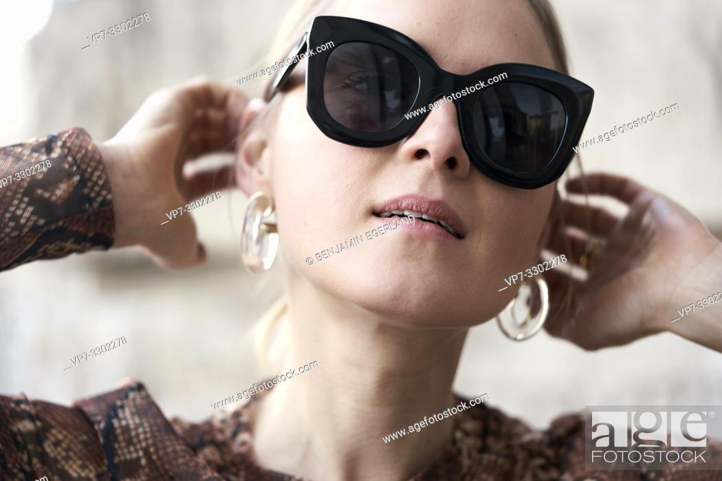 Stock Photo: fashionable woman wearing stylish plastic earrings, in Munich, Germany.