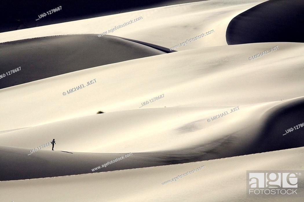 Stock Photo: A hiker climbs up the steep slopes of Eureka Dunes at Death Valley National Park, California.
