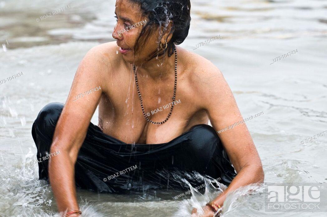 Stock Photo: An Indian woman bathing in the holy water of Gangasagar island during the annual Gangasagar mela.