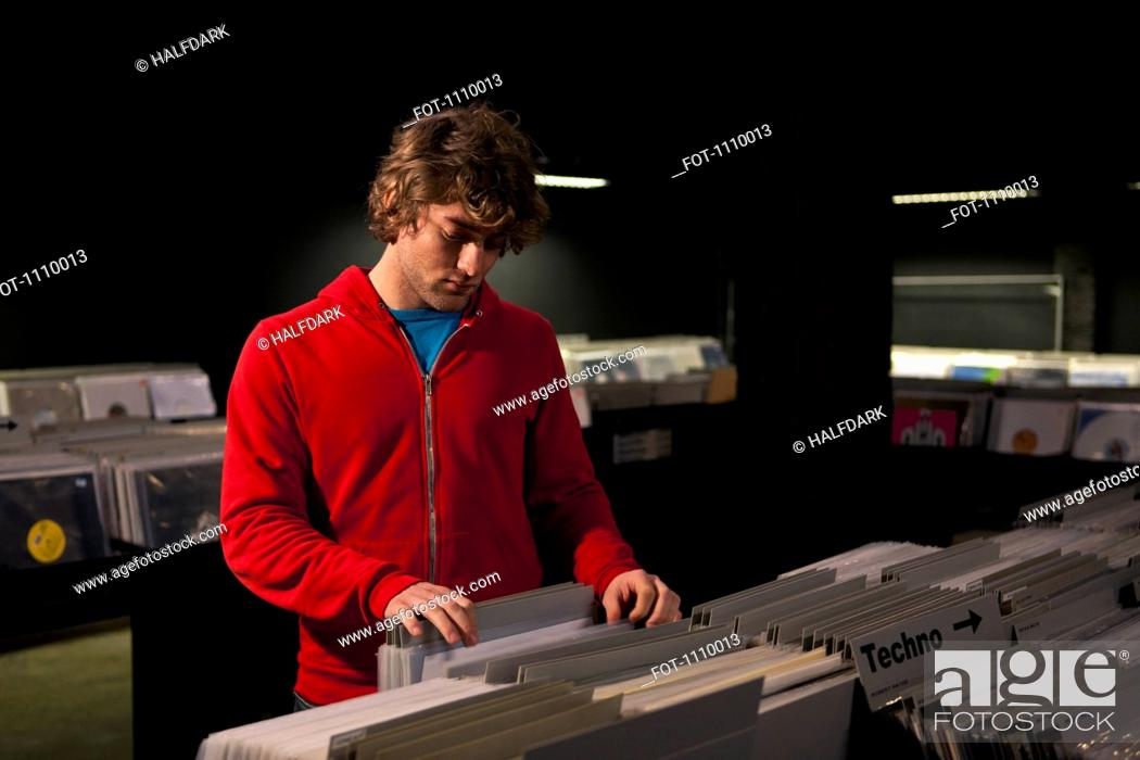 Stock Photo: A young man searching through records in a darkened record shop.