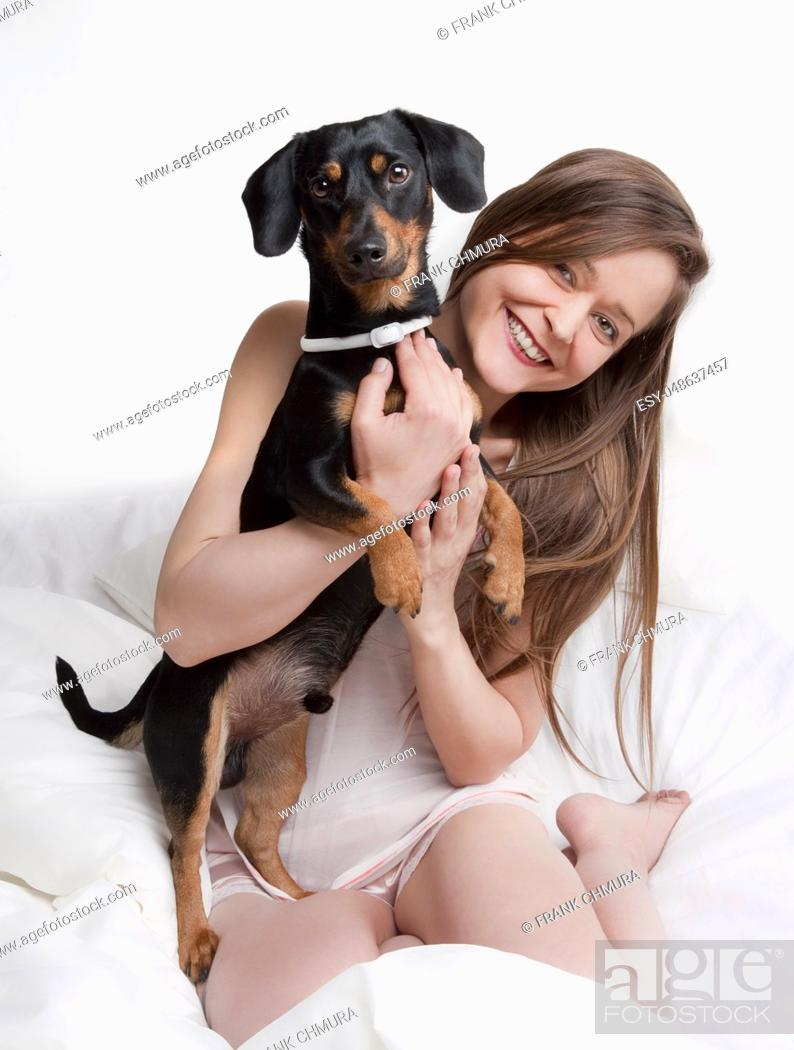 Stock Photo: Woman in bed holding her dog.