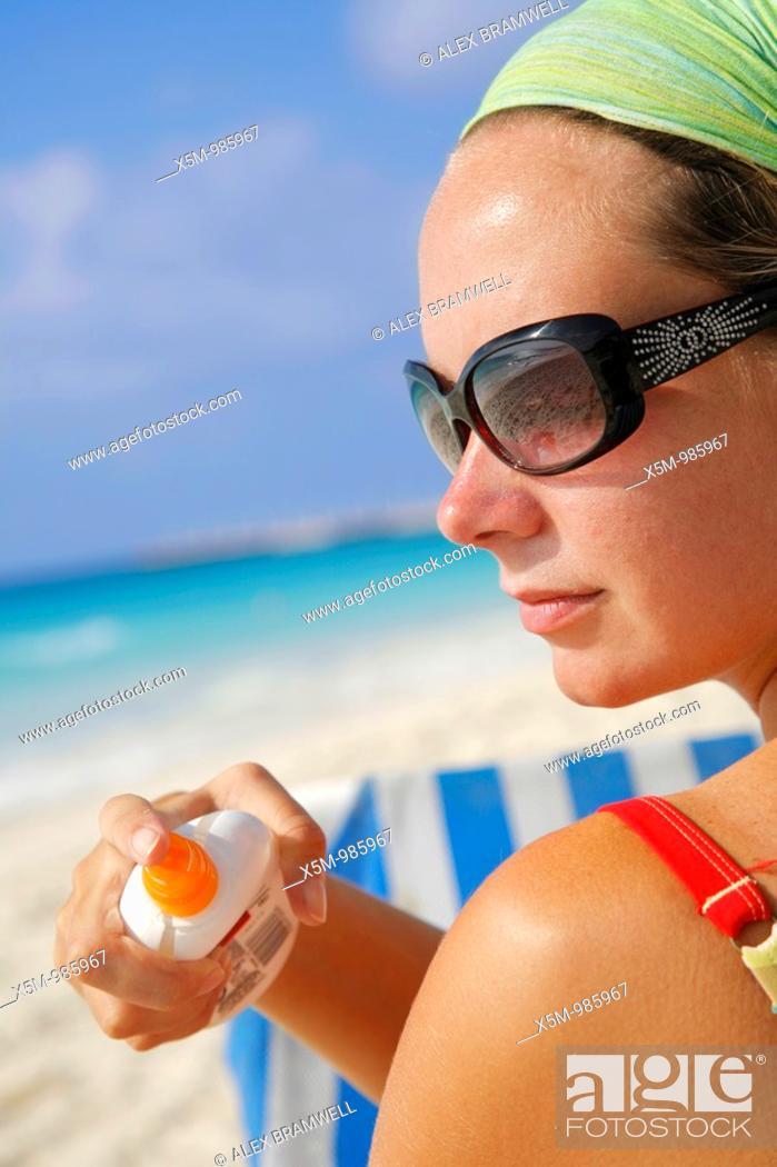 Stock Photo: Woman in sunglasses applying suntan lotion on a Caribbean beach.