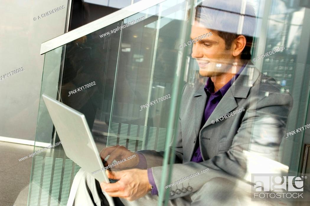 Stock Photo: Businessman sitting on a staircase and using a laptop.