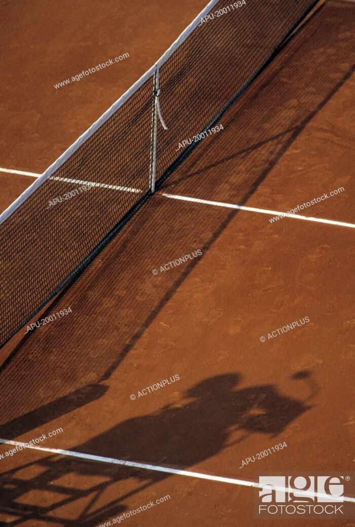 Stock Photo: Tennis net in a clay court with umpires chair shadow.