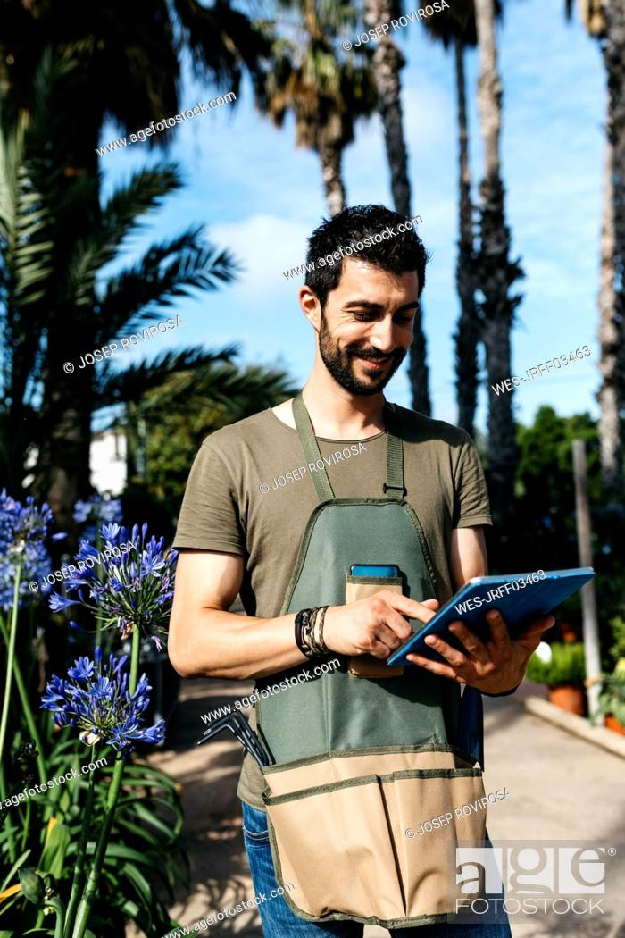 Photo de stock: Smiling worker in a garden center using a tablet.