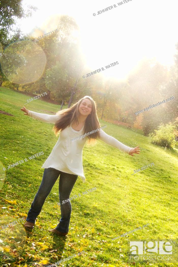 Stock Photo: A smiling teen girl playing in the rain outdoors.