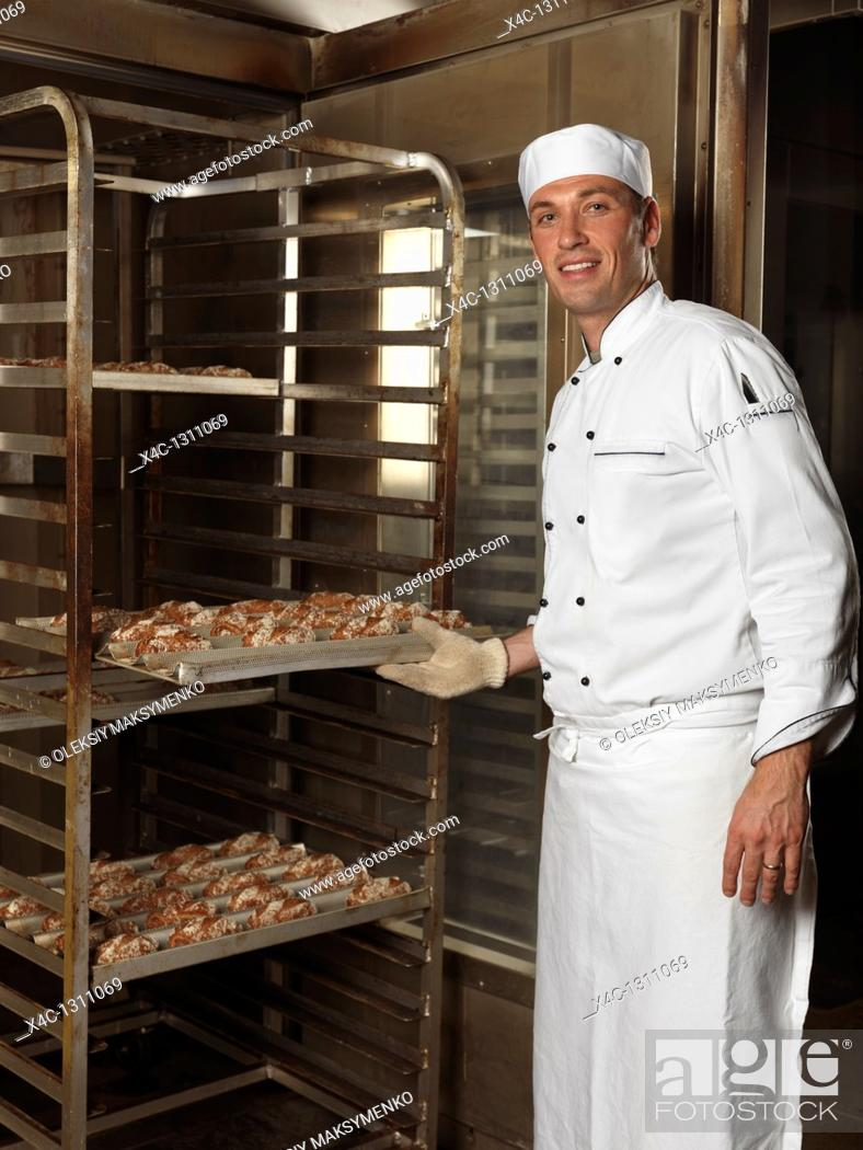 Stock Photo: Portrait of a baker taking out a rack trolley with freshly baked buns out of a bakery oven.