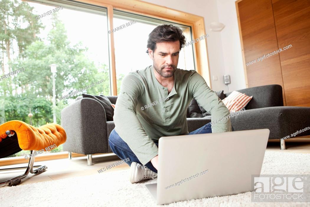 Stock Photo: Germany, Bavaria, Nuremberg, Mature man using laptop in living room.