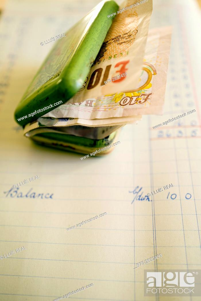Stock Photo: Close-up of a tin box filled with money (Pounds sterling) on an account book with the word Balance written on it. England.