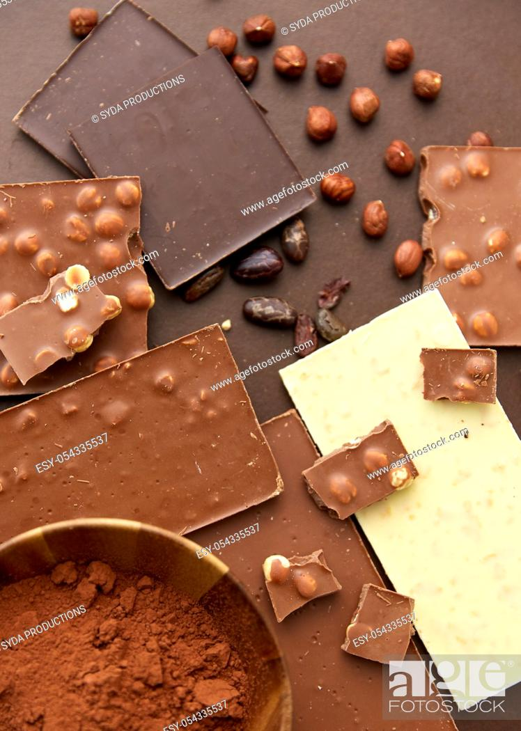 Stock Photo: chocolate with hazelnuts, cocoa beans and powder.