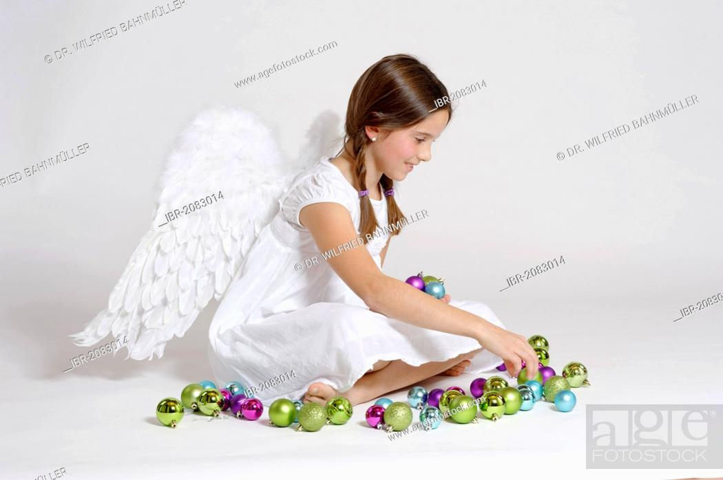 Stock Photo: Girl dressed up as Christmas angel, Christ Child with Christmas baubles.
