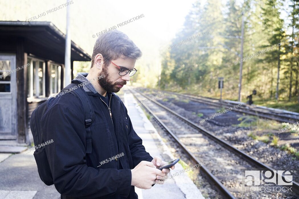 Stock Photo: Man using his phone while waiting for a train in train station. Eibsee, Bavaria, Germany.