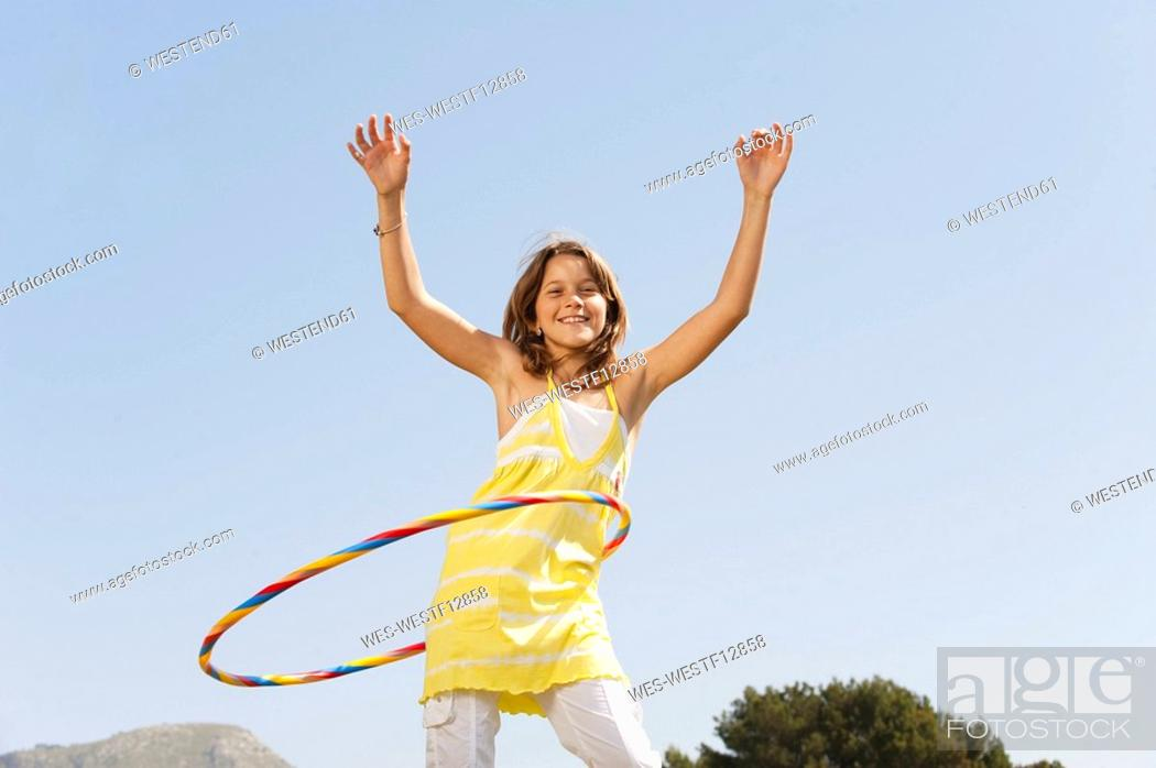 Stock Photo: Spain, Mallorca, Girl 10-11 playing with hula hoop.