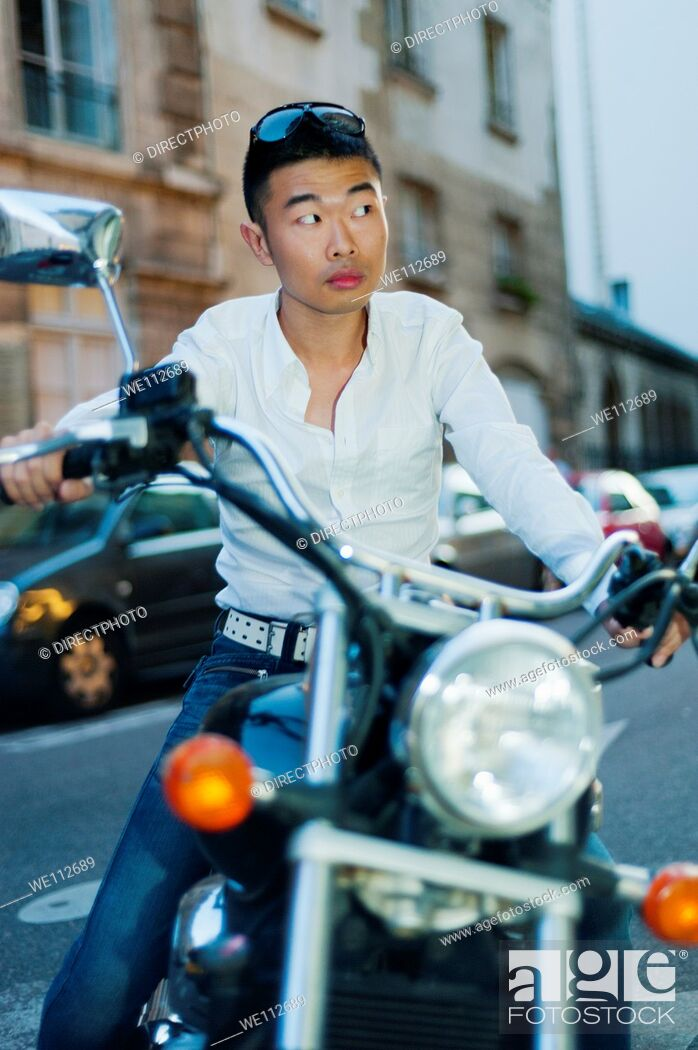 Stock Photo: Paris, France, Young Asian Man Sitting on Vintage Motorcycle on Street in St. Germain des Prés District.