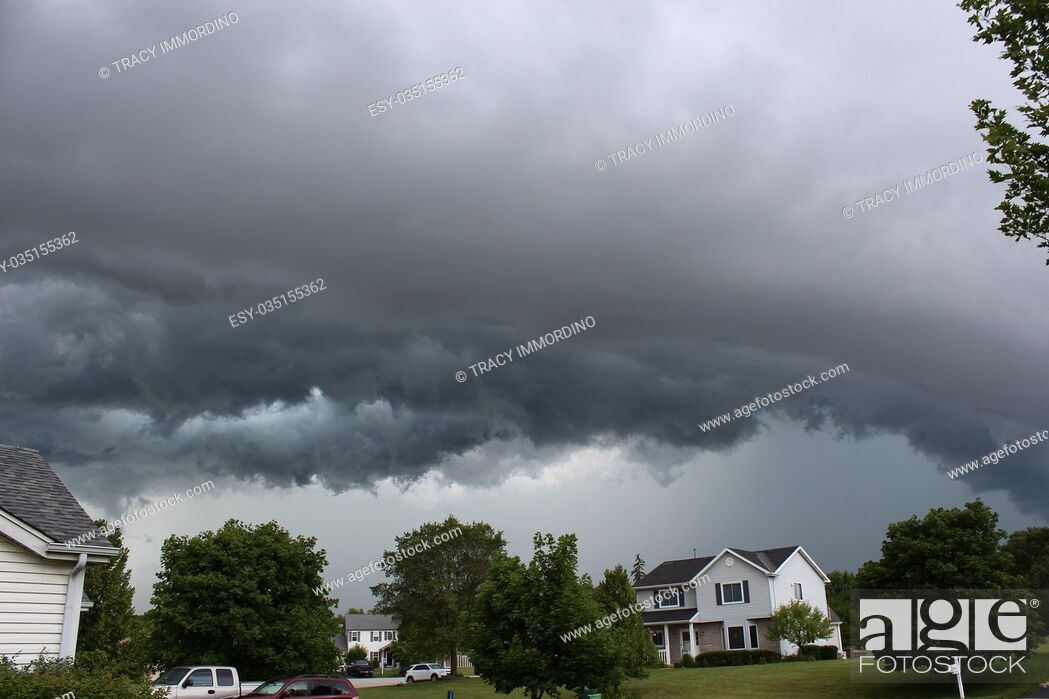 Stock Photo: A storm front of clouds arching over a suburban neighborhood in Wisconsin.