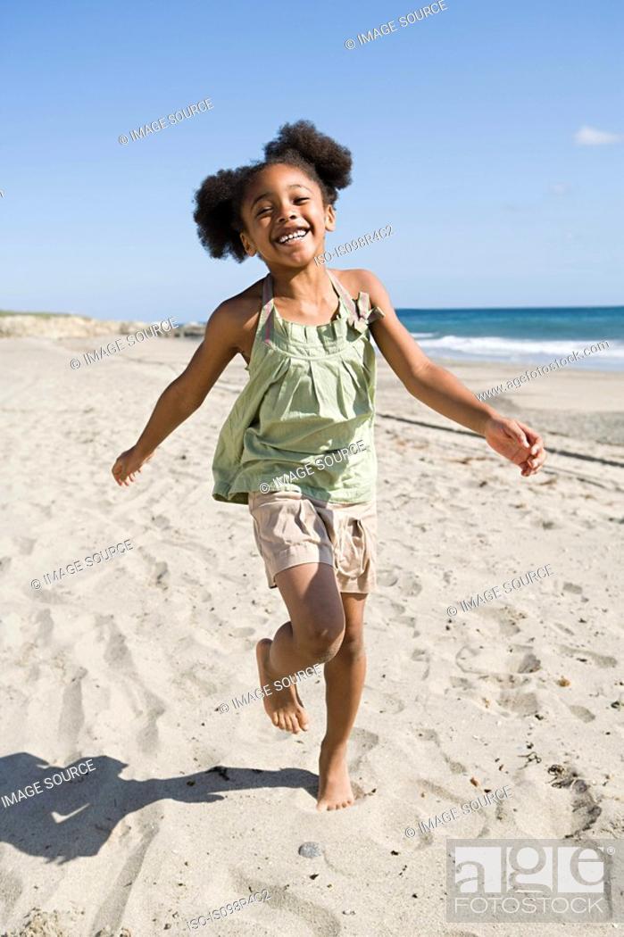 Stock Photo: Girl running on a sandy beach.