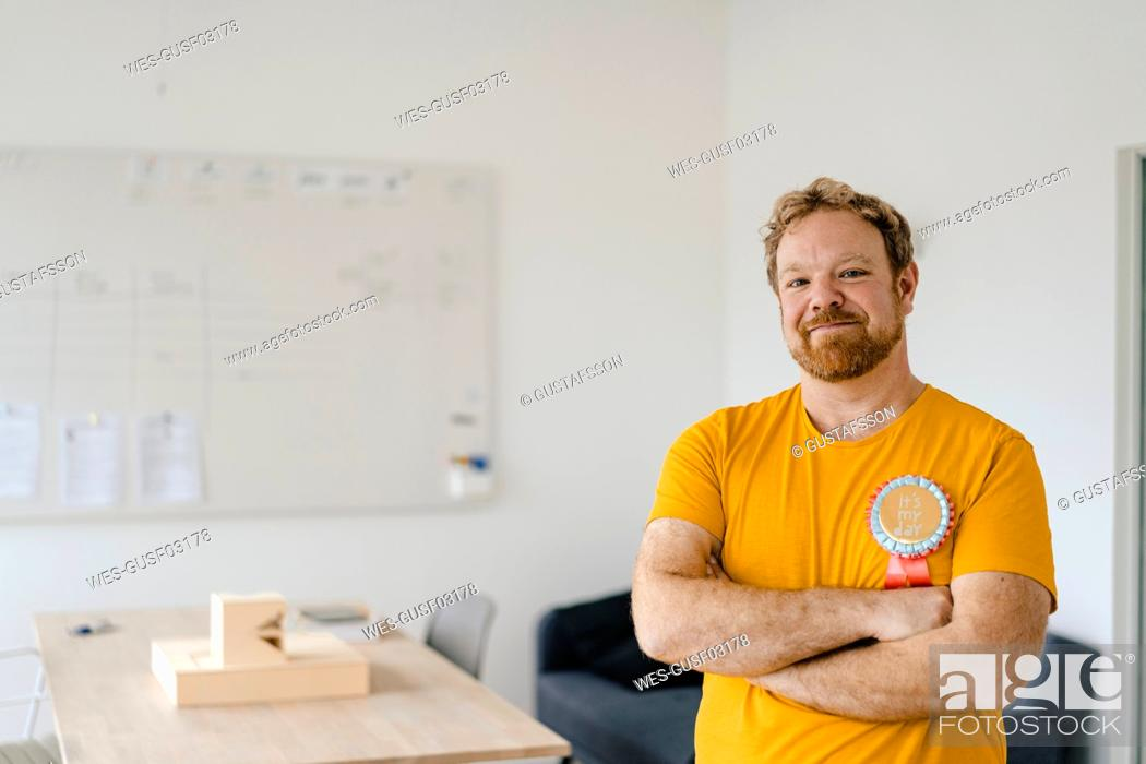 Stock Photo: Portrait of a confident casual businessman with an award in office.