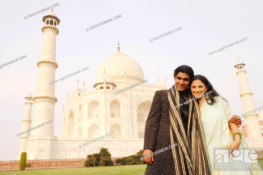 Stock Photo: Young couple standing in front of a mausoleum, Taj Mahal, Agra, Uttar Pradesh, India.