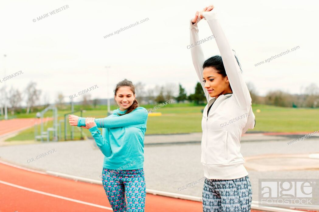 Stock Photo: Two young women on running track, exercising, stretching.