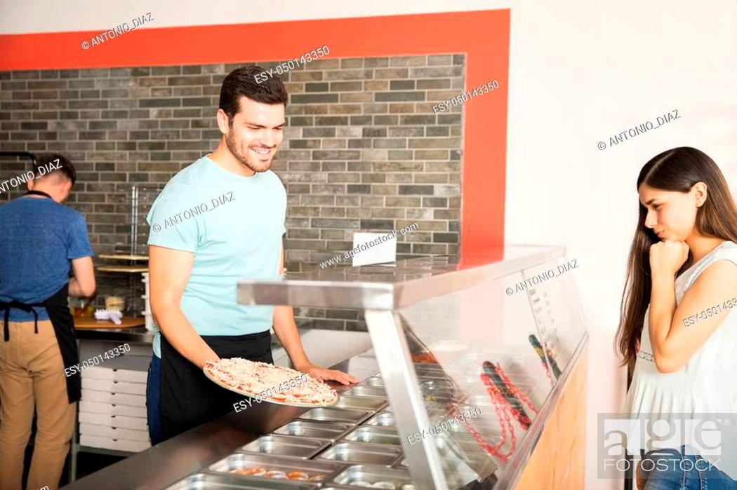 Stock Photo: Smiling handsome chef holding freshly baked pizza helping customer choose extra toppings.