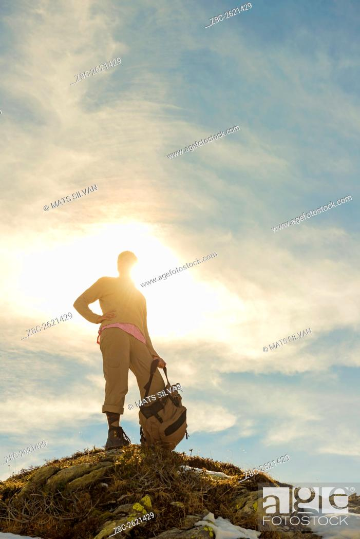 Stock Photo: Woman with her backpack standing on a mountain top and sunshine in Grisons, Switzerland.