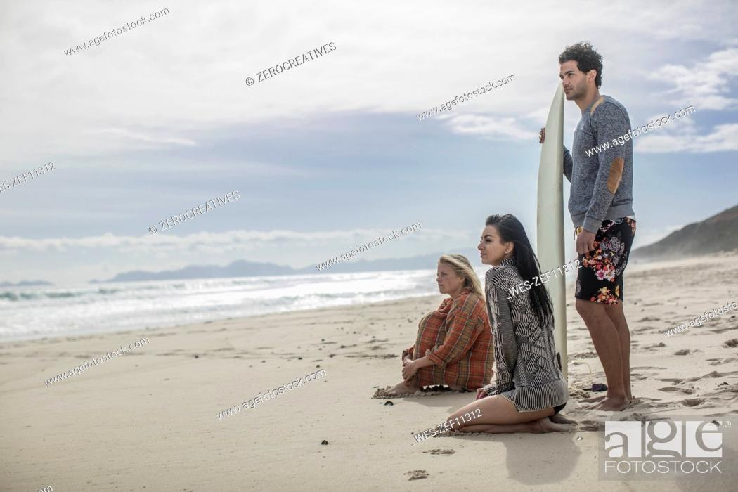 Stock Photo: Friends with surfboard together on the beach.