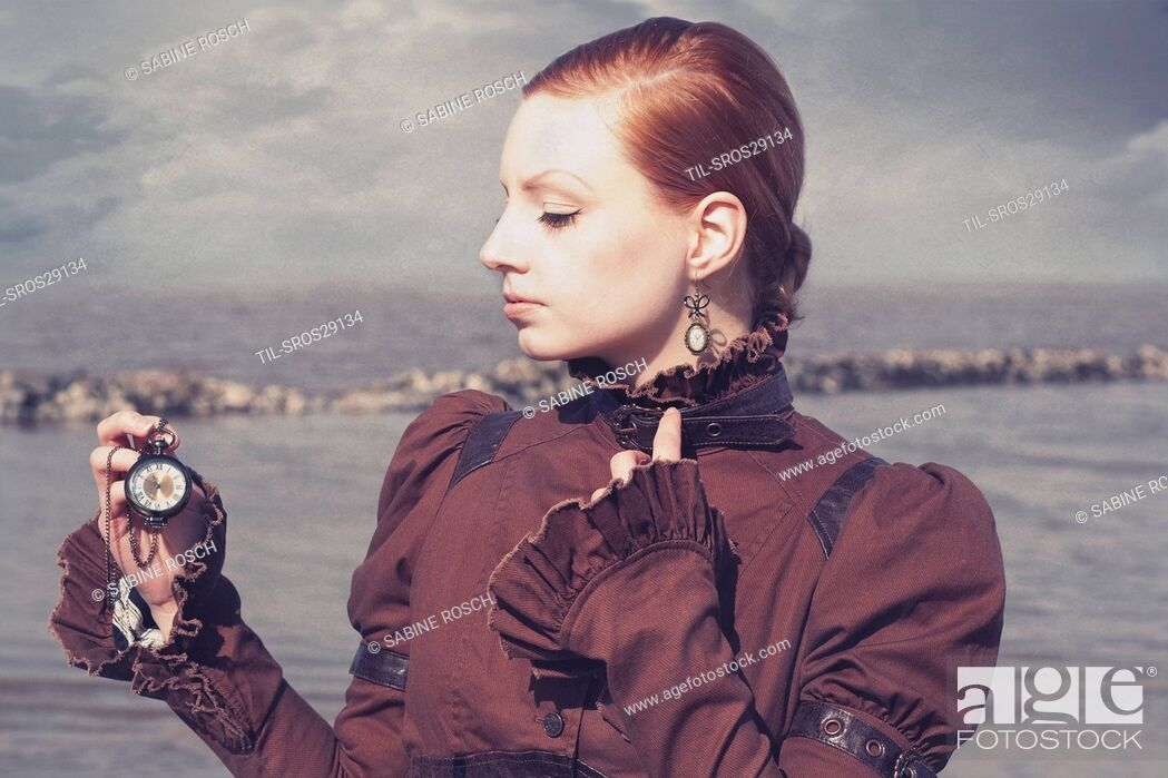 Imagen: Young woman in a victorian dress standing alone outdoors beside the sea and holding a pocket watch in her hand.