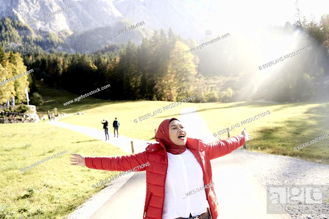 Stock Photo: Asian woman with hijab feeling free, enjoying trip to nature, feeling of deciding to choose one of two separate pathways.