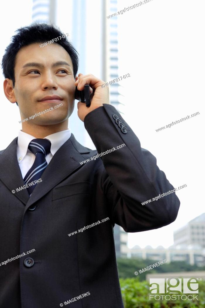 Stock Photo: Businessman conversing on a cellphone, portrait.