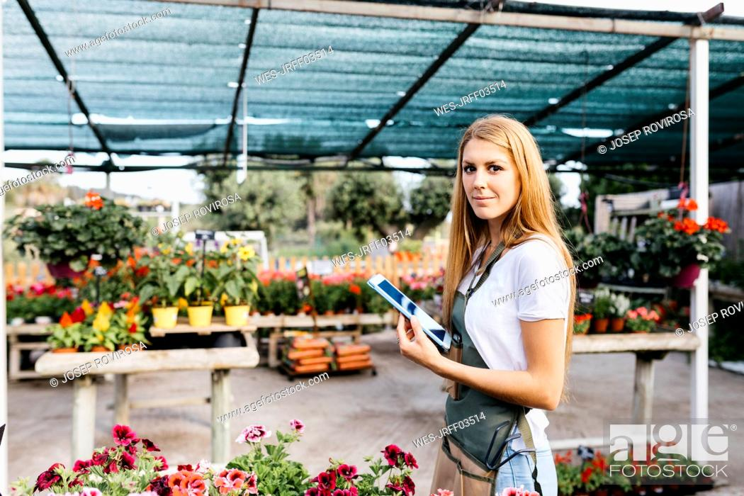 Stock Photo: Portrait of a smiling female worker in a garden center holding a tablet.