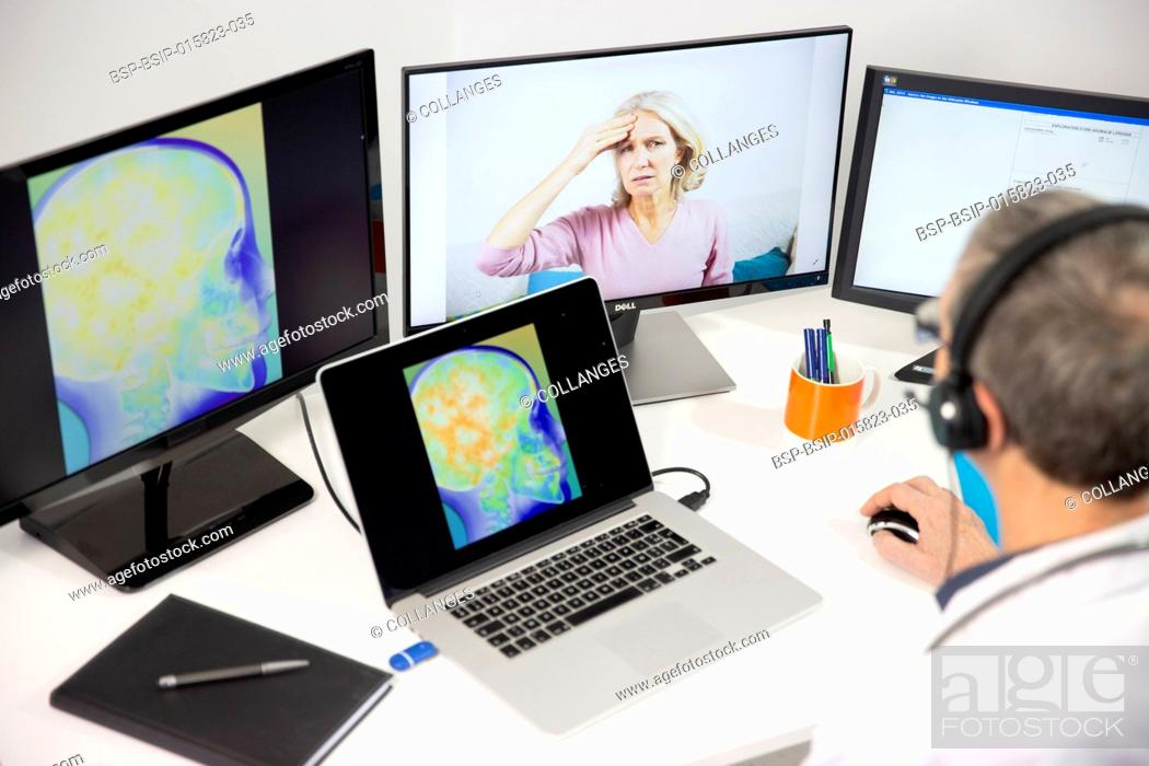 Stock Photo: A GP during a video consultation with a 45-year old woman for head pain. An x-ray of her brain can be seen on the screen.