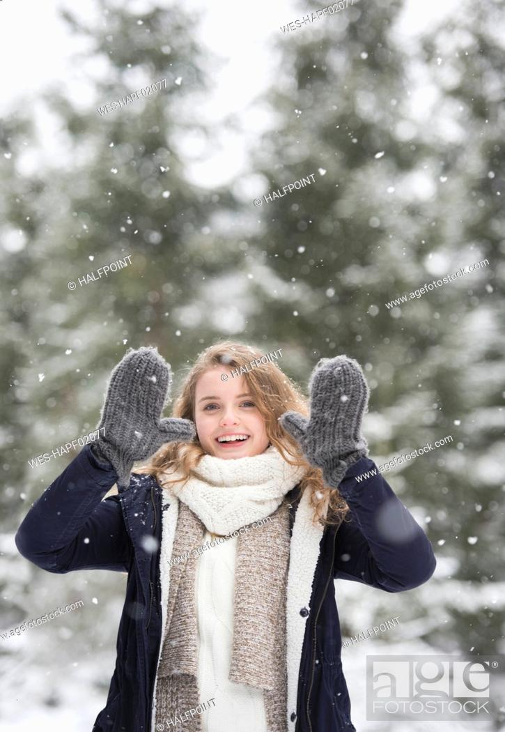 Photo de stock: Portrait of happy young woman at snowfall in nature.