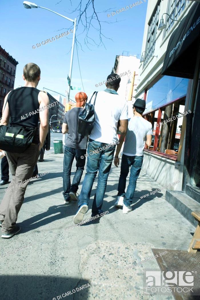 Stock Photo: Young men walking NE along sidewalk on 8th Avenue in Chelsea, New York City, rear view.