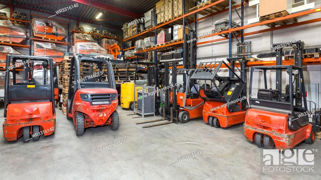 Stock Photo: Forklift machinery in a row in warehouse.