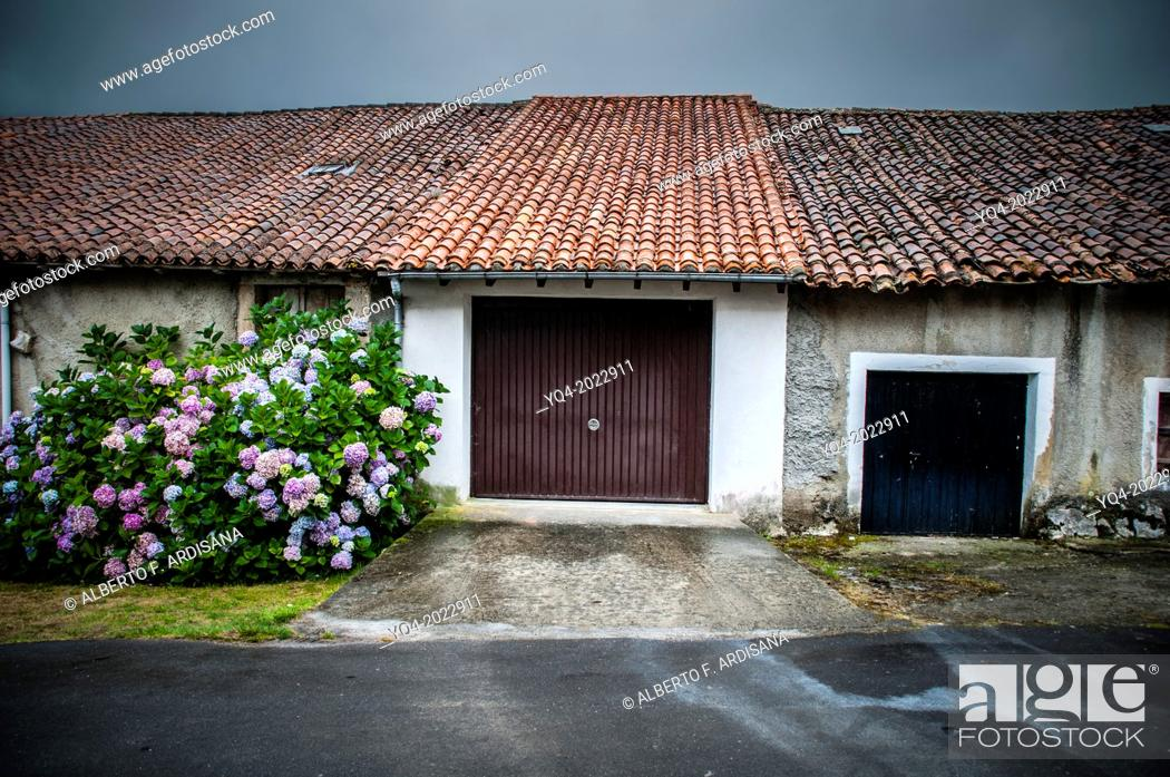 Stock Photo: Garage of a village house with typical roof, a rainy day. Asturias. Spain.