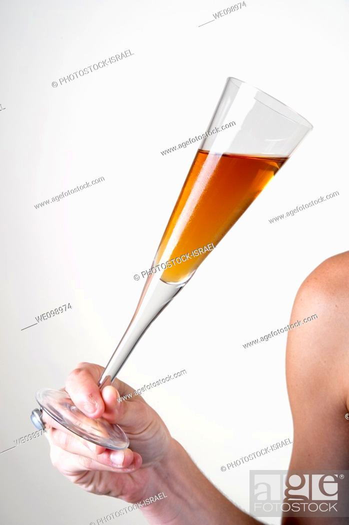 Stock Photo: young Woman's shoulder arm and hand holding a cocktail glass at an event.