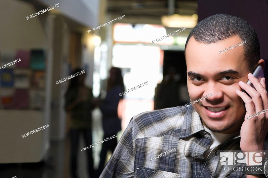 Stock Photo: Portrait of a young man talking on a mobile phone and smiling.