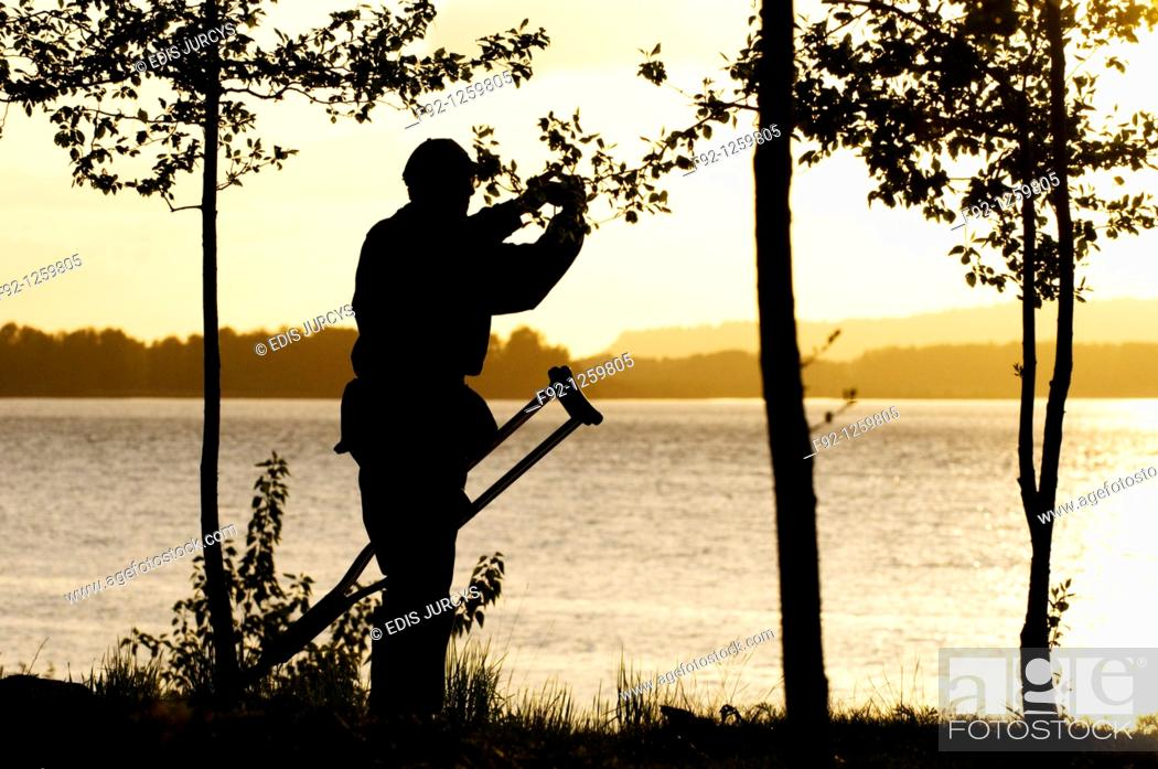 Stock Photo: Disable man is taking a photograph of the sunset at the Columbia river, Oregon, USA.