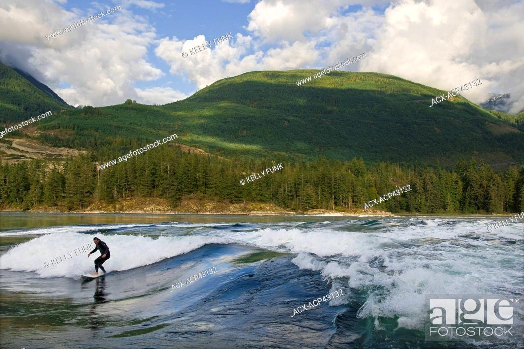 Stock Photo: A surfer rides the waves at Skookumchuck Provincial park, near Egmont, Sunshine coast, Vancouver coast and mountain range, British Columbia, Canada.