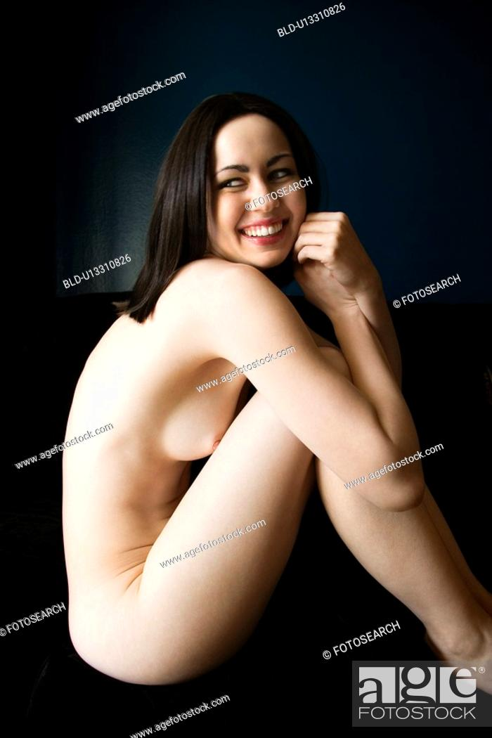 Stock Photo: Nude young adult Caucasian woman sitting and smiling.