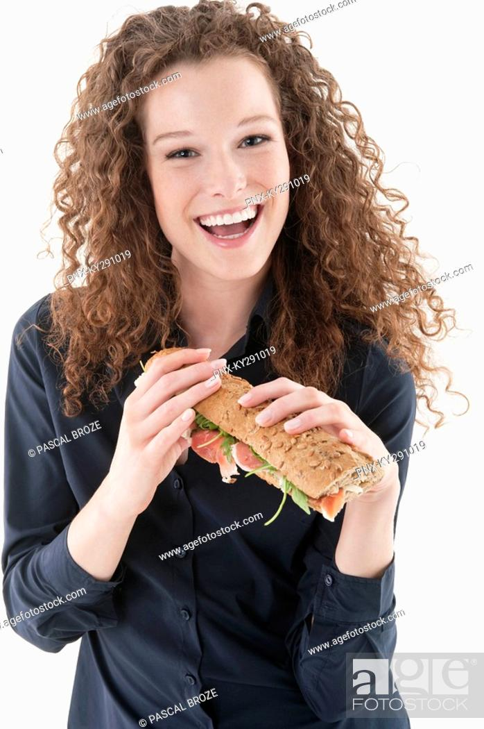 Stock Photo: Woman holding a sandwich and laughing.