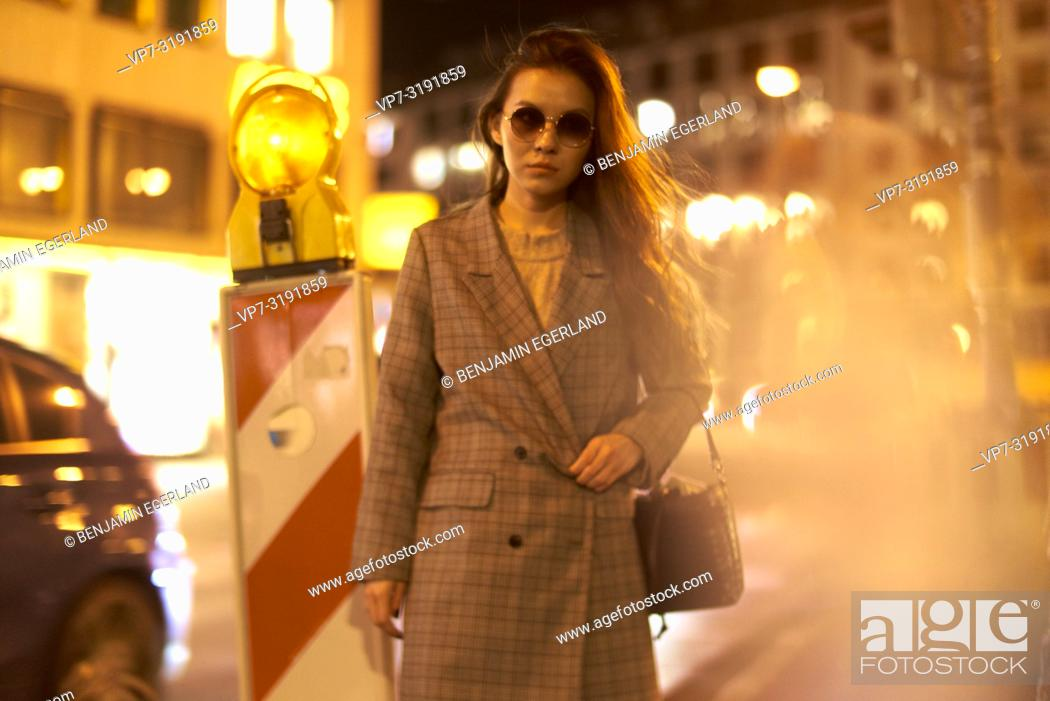Stock Photo: Fashionable woman on the street by night. Munich, Bavaria, Germany.
