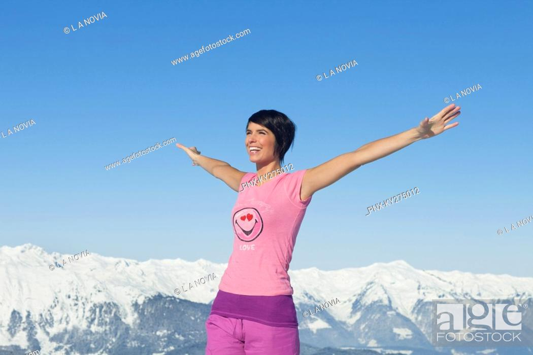 Stock Photo: Young smiling woman with arms raised, mountains in background.